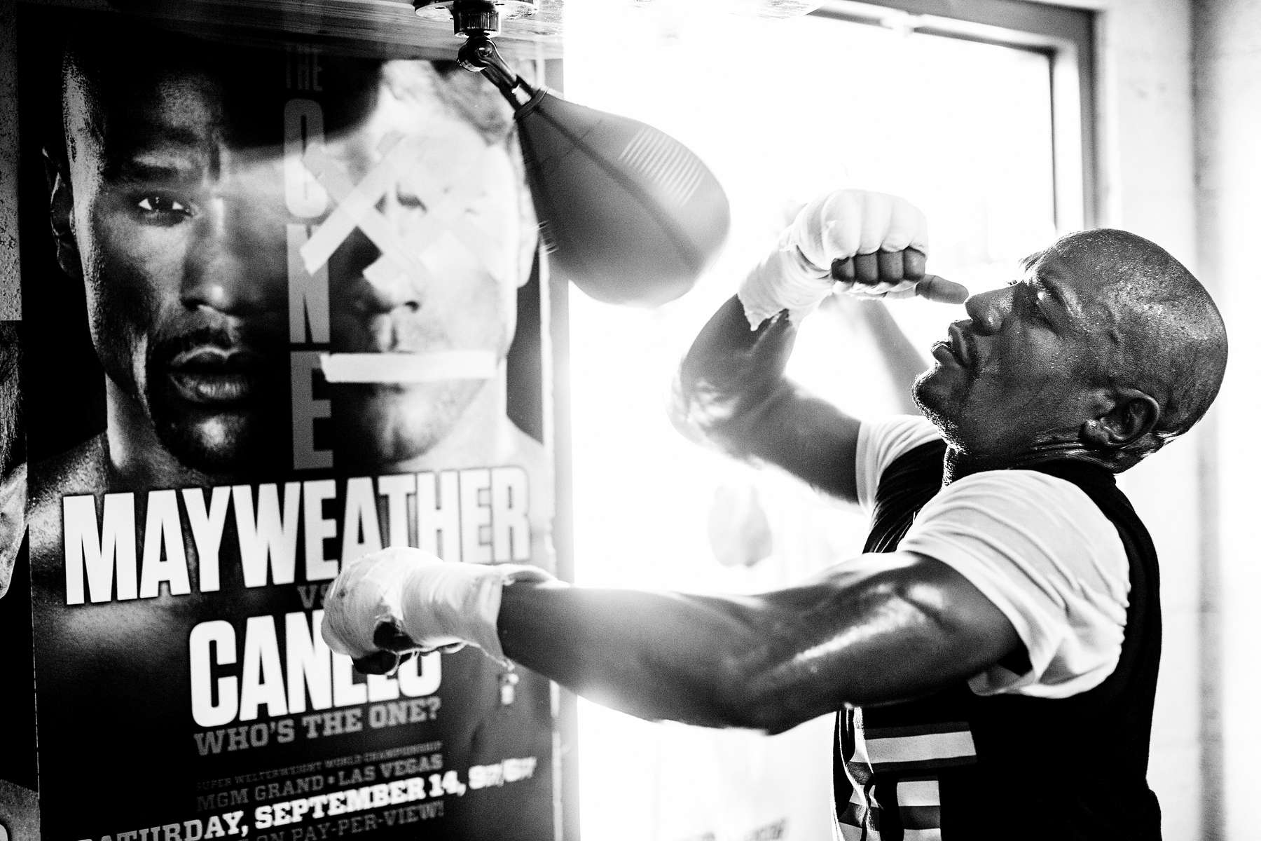 LAS VEGAS, NV - JULY 26: After instructing his cut man to tape over Alvarez's eyes and mouth on a fight poster, Mayweather works the speed bag in his Las Vegas gym.(Photo by Benjamin Lowy/Reportage by Getty Images)