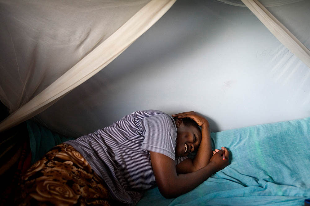 Lato Caroline Gilisho, 17, inside her dormroom at the Tasaru Safehouse for Girls December 19 in Narok, Kenya. The Tasaru Safehouse supports board, lodging and education of young Maasai girls from preteens to late teens who seek refuge from female circumcision and early marriage. Caroline arrived at the center at the age of thirteen to escape an arranged marriage. Instead of using the money given to her for groceries and supplies for the ceremony, she used it to pay for her fare to Narok. She is currently in her last year of school and serves as a class prefect. While inherently bright, she is also a hardworker. Caro, as her friends call her, wakes up at around 3:30 in the morning during school holidays to study. Her parents continue to refuse her despite numerous interventions by Tasaru counselors. One counselor recalled Caro saying that after she finishes school and becomes an important leader in the community, she will drive back to her village in her own car to visit her parents. Although rejected by her own family, Caro harbors no ill will towards them. She continues to value her Maasai roots though feels strongly against FGM and early marriage. She hopes to one day go back to her community and serve as a positive influence for a younger generation of girls.