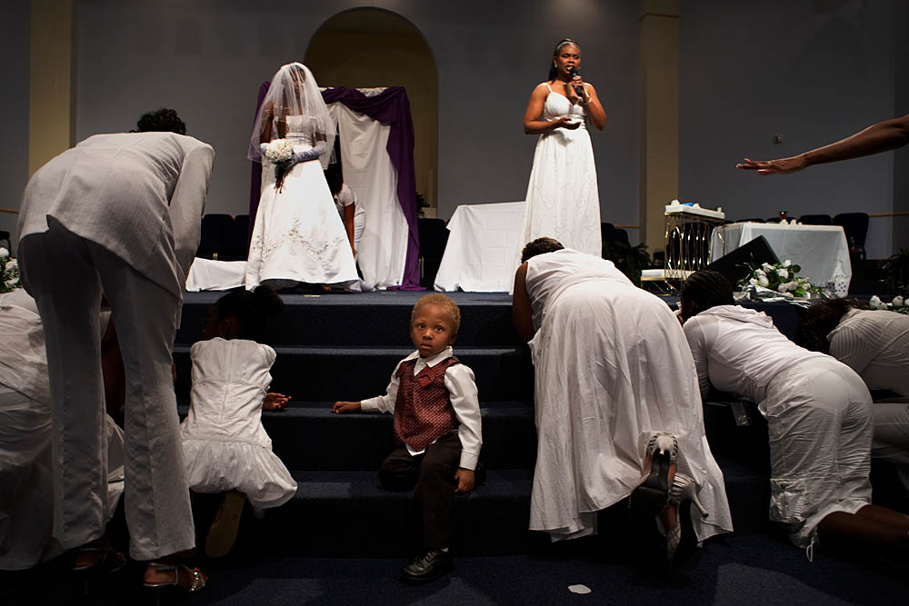 Congregants pray at the altar during the Purity Ring Ceremony at the Destiny World Church June 16 in Austell, GA. Young children, teenagers and their parents or guardians came together for three days to promote abstinence. Issues like STDs, peer pressure, teen pregnancy,  molestation and abuse were also main topics of panel discussions. The Holywood Retreat concluded with a Purity Ring Ceremony where each participant pledged to keep their virginity or to no longer participate in sex outside of marriage by wearing a {quote}purity ring{quote} on their wedding finger until the day it is replaced by a wedding ring. The three day event featured ministers and lay speakers, a fashion show that illustrated how one can remain modest and fashionable, a religious concert as well as other activities that entertained a predominantly young and energetic group.