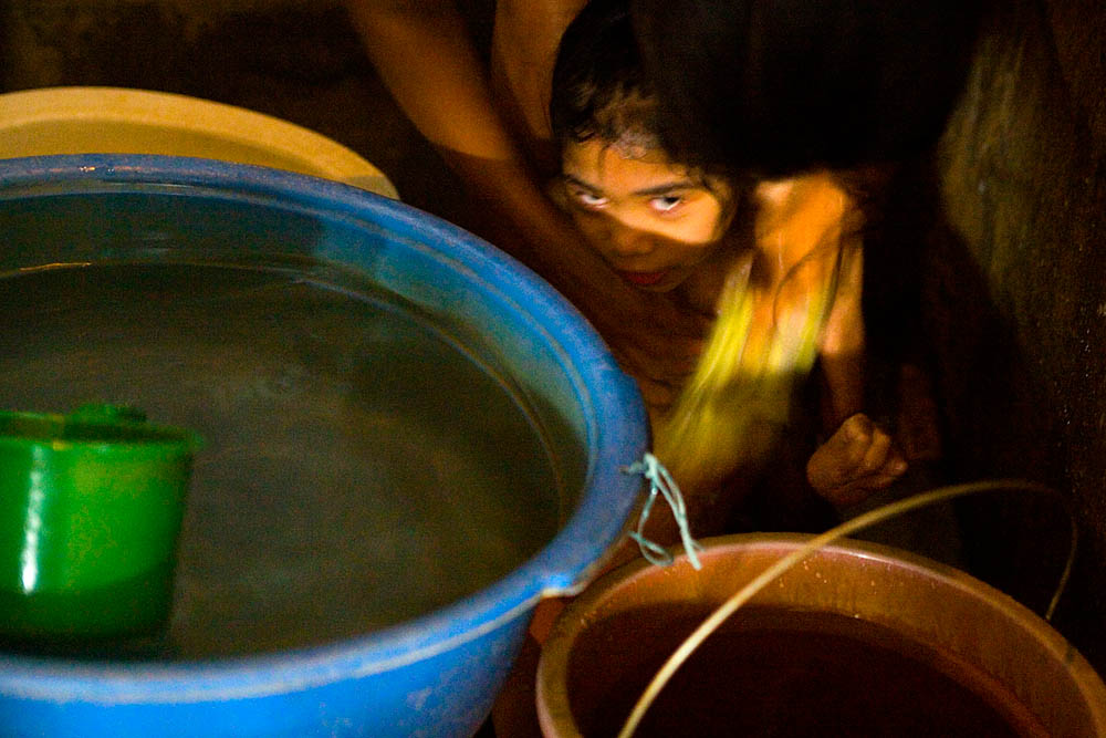 Diane Liwanag, 12, is bathed by her mother.