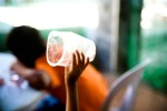 Rose Ann Calma, 8, plays with a plastic cup as she is craddled by her mother.
