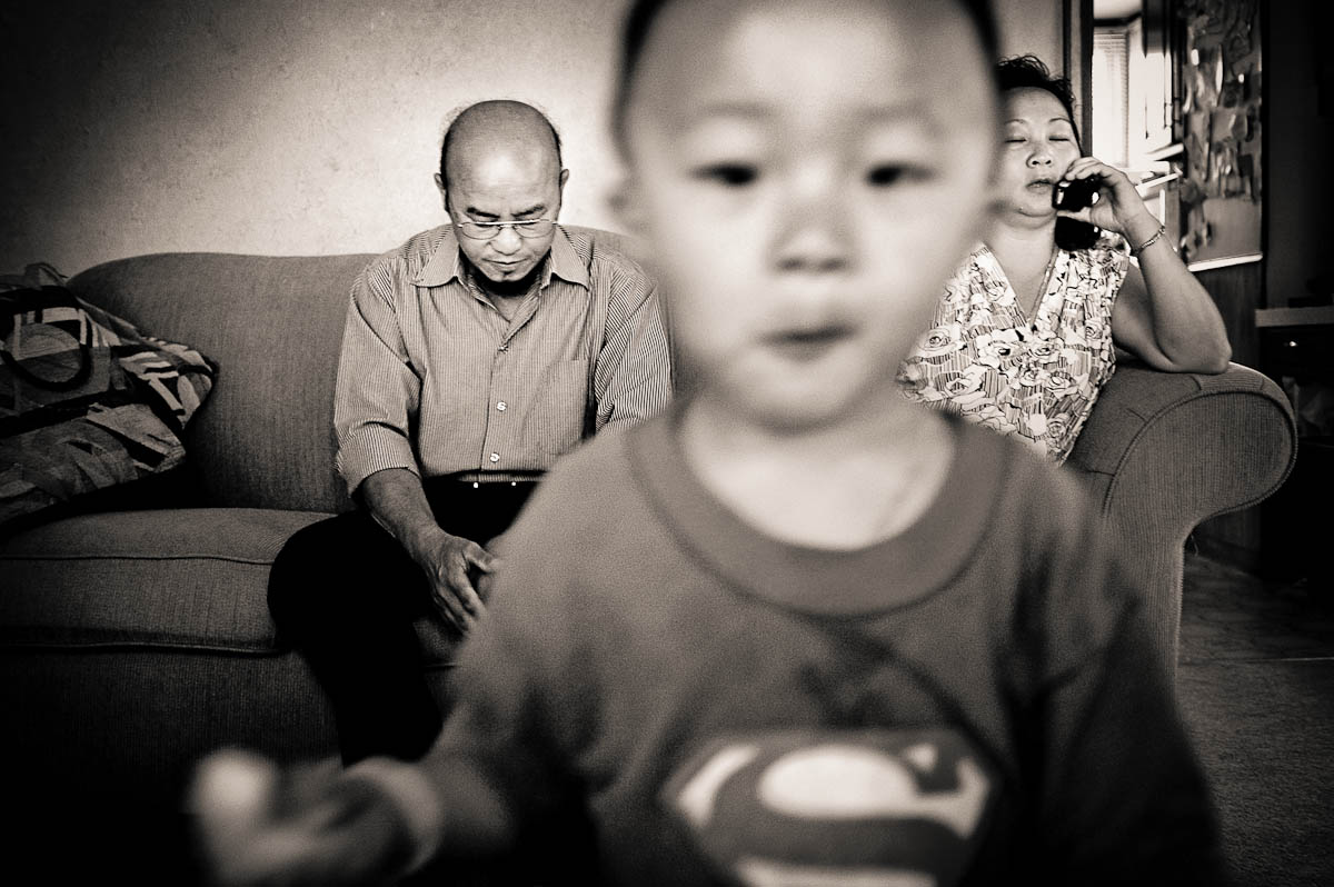 As 2-year old Alex Lee plays in foreground, his grandparents Jai Lor, left, and Choua Moua sit on the couch back at their daughter's home in Minnesota. They returned after so far being unsuccessful in finding a chicken farm. Instead they were slowly draining their savings and living in a small apartment in Gentry, Arkansas. {quote}I'm an old man, I only do a secret cry,{quote} said Jai.