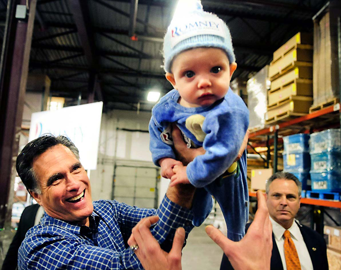 Republican presidential candidate Mitt Romney left, hands 6-month-old Dexter Hall of Plymouth, Minn. back to his mother, Laura, during a campaign stop at Freightmasters, Inc. in Eagan, Minn., on Wednesday, Feb. 1, 2012.