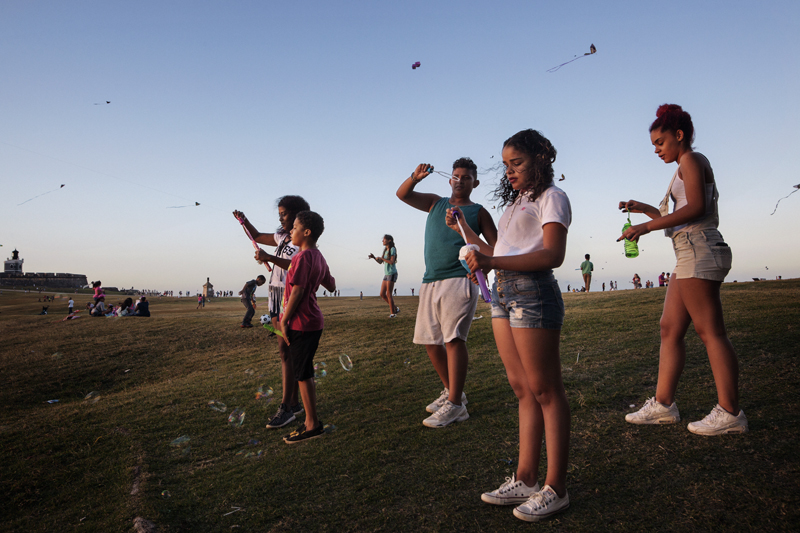 People are enjoying a relaxing Sunday afternoon in the park surrounding San Felipe del Morro Fortress in Old San Juan.