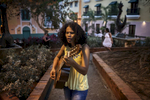 A young girl is playing guitar in the tiny streets of Old San Juan.