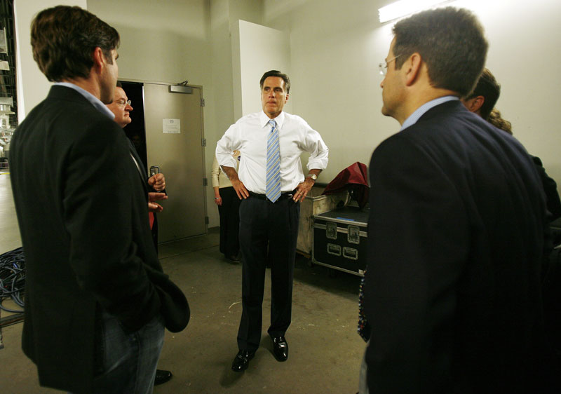 Republican presidential candidate Mitt Romney speaks with campaign advisors after the Massachusetts primary.