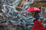 A woman is seen walking by graffiti on a wall in the Williamsburg neighborhood of the borough of Brooklyn in New York, September 16, 2014. The photo was take through raindrops on the window of car. REUTERS/Shannon Stapleton (UNITED STATES