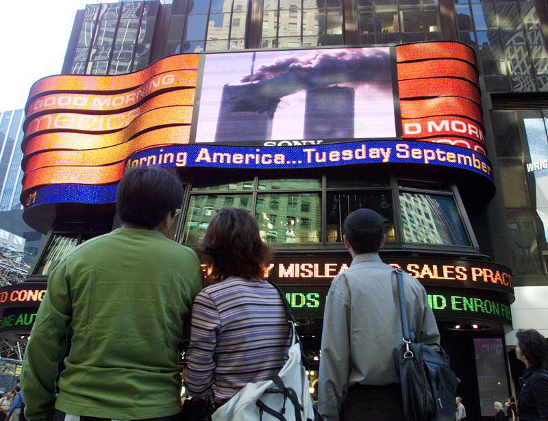 People gaze at a jumbotron in Times Square after the first tower of the World Trade Center was attacked on September 11, 2001.