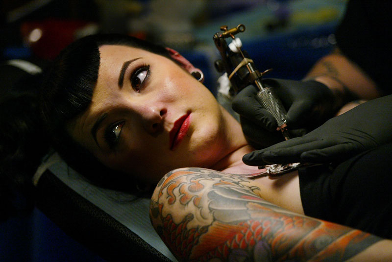 A woman gets a tattoo applied during that tattoo expo in New York City.