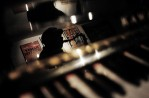 Reflected in the piano at his club, Bill Saxton performs in the space that housed a speakeasy and hosted Billie Holiday's debut.