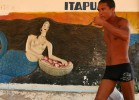 A fisherman passes a mural of Iemanja, the Candomble orisha honored as Goddess of the Seas.
