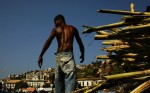 On the city docks, a young man unloads sugarcane, a crop introduced by the Portuguese almost 500 years ago. Sugarcane bears the weight of its history, from the initial enslavement of indigenous Brazilians and subsequent importation of African slaves to today, where crops are increasing to feed demand for ethanol.