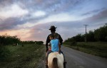 Riding with two of his grandsons, Joao de Boi, John of the Bull, goes to water his cattle before sunset.