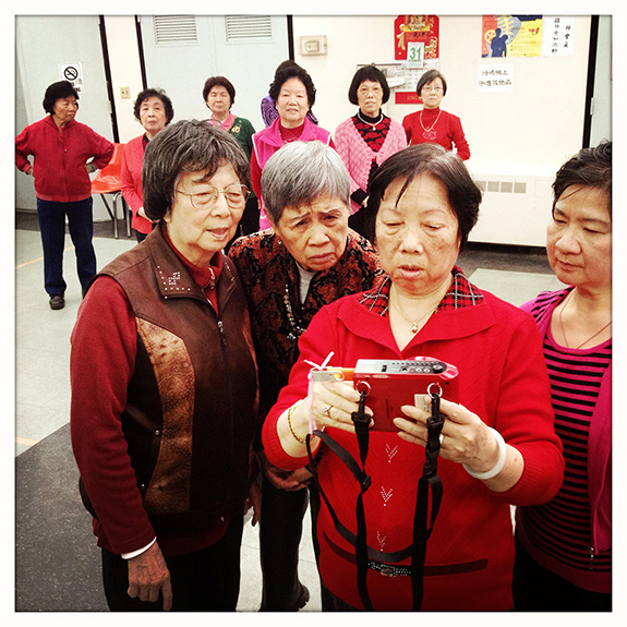 "At 83, Chan Kwai Ken, known as Mrs. Eng (pictured in front, left) comes to the Mulberry Street Senior Center twice a week to attend the singing and dancing group she founded 15 years ago. A former kindergarten teacher in her native Guangzhou, she found work in Chinatown's laundry and restaurant business, and retired when her health began to fail. Sitting at home idly left her feeling depressed: ""I used to love playing the piano, and singing and dancing with the children, and I wanted to do something for the community. So I thought, this is what I'm good at."" The Mulberry Street senior center is run by the Chinese-American Planning Council, a community-based organization dating back to the mid-1960s era of the War on Poverty and the unprecedented growth of NYC's Chinese community after the 1965 immigration reform. Located in the heart of historic Chinatown, across from Columbus Park, it serves 500 Chinese-speaking seniors daily. Over the years, Mrs. Eng's group has grown from its initial 12 participants to over 50 members, mostly women. She can no longer move as easily and her eyesight is faltering, so she has turned over the leadership to someone younger – although she still likes to keep an eye on things and loves to sing the old folk songs. {quote}My body is disabled, but my heart is not. I am happy when I'm here.{quote}"