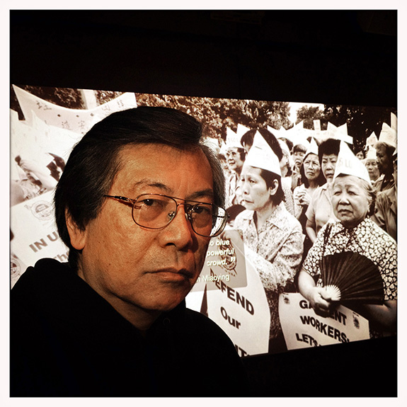 "Corky Lee poses with his 1982 photograph of striking garment workers, featured in the New York Historical Society's exhibition Chinese American: Exclusion/Inclusion. ""It was the largest Chinese garment worker rally in the history of NYC. 15,000 showed up to lobby for a new contract – it was pretty monumental. Fifteen, twenty years after that, the garment industry is no longer a viable employment source for the Chinese immigrant community, but back in the day, at least one person in the family had to work for the union, because that was the source of health insurance. Because there was absolutely no health insurance in the laundries and restaurants."" Corky was still in high school when he began noticing the absence of Chinese Americans in the media and newspapers around him – even the historic photograph of the completion of the transcontinental railroad, built by Chinese labor, didn't have any Chinese workers in it. He has been committed to making his community visible ever since, photographing not only Chinatown but Asian America for more than four decades. The 68 y.o. Queens native has been the country's self-appointed, undisputed, Unofficial Asian American Photographer Laureate for so long that even the post office agrees: a letter addressed to just this title in ""Elmhurst, Queens"" actually found its way to the photographer."