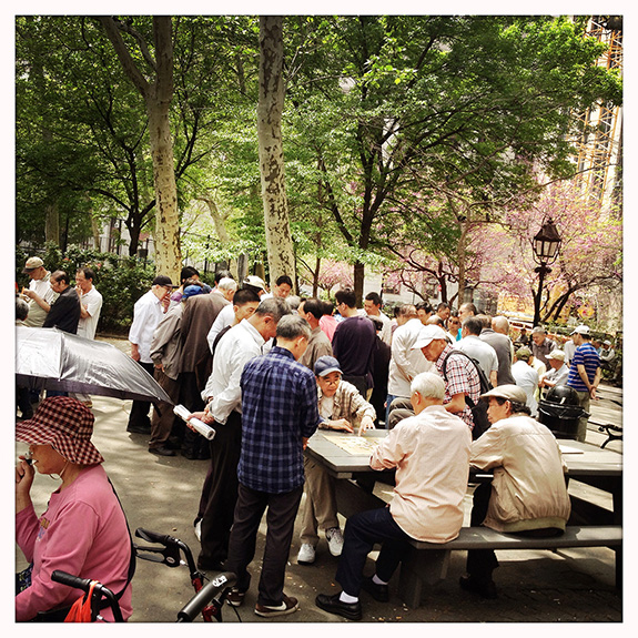 "Columbus Park in the heart of historic Chinatown functions as an informal senior center not just for people living in the neighborhood, but those who have moved away and are stopping by to chat, play cards or Xiàngqí, Chinese chess. CPC's Chinatown Senior Citizens Center across Mulberry Street offers free meals and programs, but while the weather allows, the park will be buzzing with activity and the sounds of competing opera groups.Fay Chew Matsuda works with seniors at Hamilton-Madison House, another neighborhood program that serves many first generation Chinese immigrants who came to the U.S. as working adults and who have aged in place. Other elders might have arrived more recently through family reunification: ""finally, because it took so long to actually 'stand in line' so to speak and get over here. Working families love to have their grandparents here so they can help take care of children. But it has created some problems, too, because what happens when those little grandchildren grow up? We've gotten to hear about situations where people feel like they were useful at a certain point, and then when the grandkids no longer needed them, feeling exploited. We're finding that elder abuse is something that we have to be very aware of in the community as well, whether it's financial, emotional, possibly physical, too. So I think there'll always be a need for people to be able to find services in their own language, that they feel comfortable with, and where the meals are culturally appropriate."""