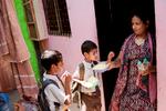 Khatija sends her two boys off to school.