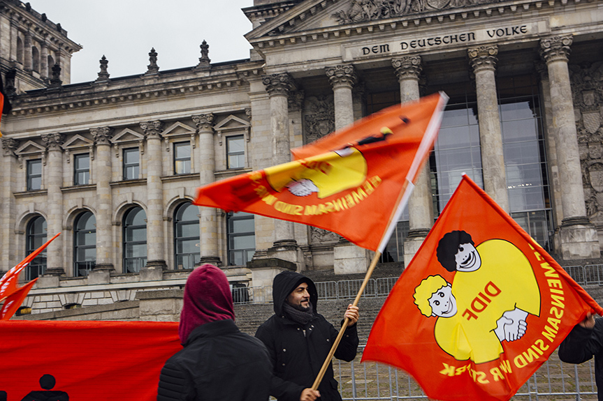 "A small rally attended by leftist parties, anti-racist youths and Turkish-German unionists outside of the Reichstag parliament building denounces the newly restrictive ""Asylbeschleunigungsgesetz"" (Asylum Acceleration Law) that was passed that day. Taking effect on November 1st, 2015, the law calls for increasing the mandatory length of a refugee's stay in an initial intake center to 6 months, while lengthening the work ban period and making access to higher education and job training more restrictive for young refugees who are granted a temporary stay of deportation, or Duldung – developments that will make integration a more difficult and lengthy process for new arrivals. The dedication Dem deutschen Volke –  To the German People – is inscribed on the Reichtag's frieze, and many of the fears and trepidation expressed by Germans who hope to clamp down on the flow of refugees to the country are going beyond economic concerns to touch on a longstanding debate over whether Germany is becoming a country that welcomes immigration and diversity."