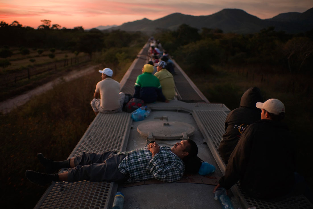 Central American migrants ride atop a freight train carrying cement as they head north in an attempt to enter the US.  Traveling by train has become more dangerous as kidnappings and robberies have risen in recent years with increased drug cartel activity.