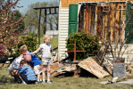 Gabe Lambert grieves the loss of his grandfather, with his children, Luka, 8, front, Anson, 6, back, and Mya, 7, right, at the site of house fire at 738 Strawberry Hill Road in Evansville on Wednesday, March 21, 2012.  Donald R. Lambert, 81, perished in the fire that destroyed his home and his neighbor's home and damaged several others in the neighborhood.  Lambert's son, Greg, not pictured, made and placed a cross to honor his father in front of the destroyed home.