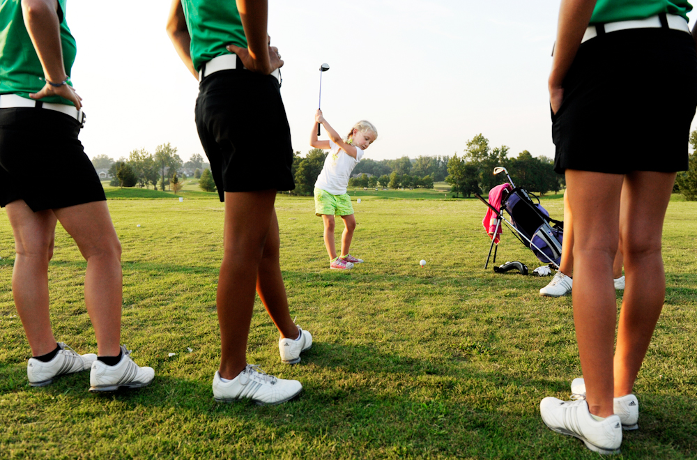Lillie Price, 5, takes a swing while members of North High School's girls golf team look on during a golf clinic at Eagle Valley Golf Club in Evansville on Wednesday, July 20, 2011.  The clinic encourages girls to start playing golf at an early age which helps feed North's high school program. Price's older sister, Olivia, 16, not pictured, plays for North.