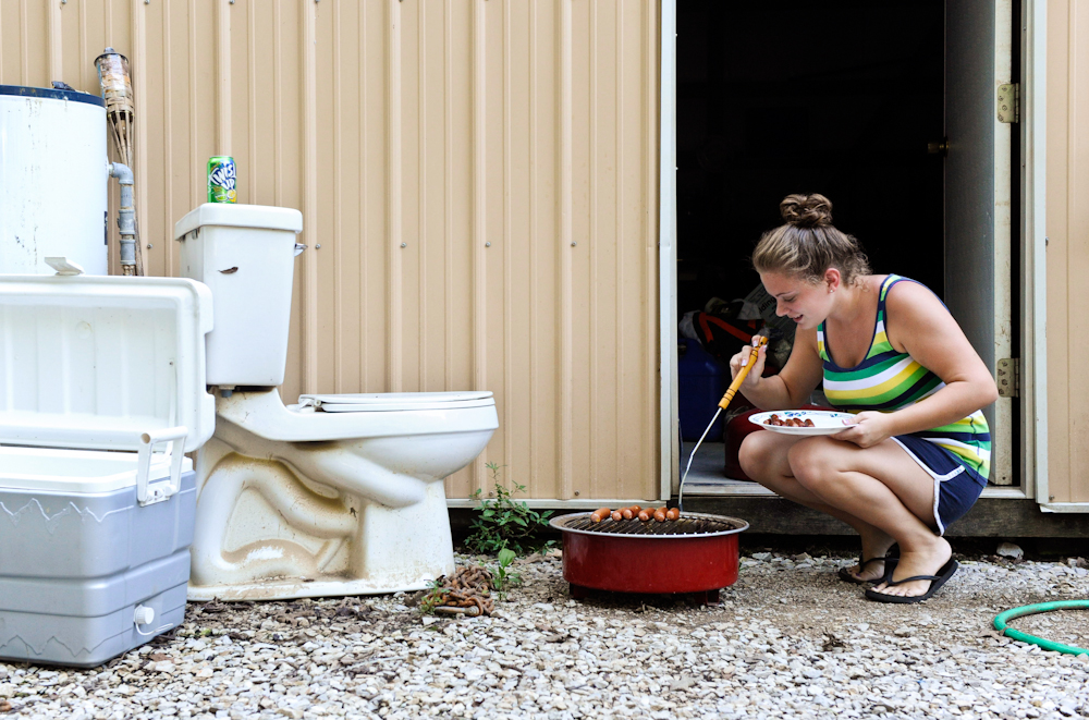 Kady Lashley, 19, grills bratwursts for dinner on her parents property in Point Township, Ind., on Monday,August 8, 2011.  The Lashley's have been living out of a travel trailer after their home flooded in the spring rains in April and May.  The commode and hot water heater, at left, were some of the items that they salvaged from their home.The family had flood insurance which proved to be inadequate.  They are hoping for FEMA assistance since several counties across the river in Kentucky and Illinois received federal aid from the same storms.