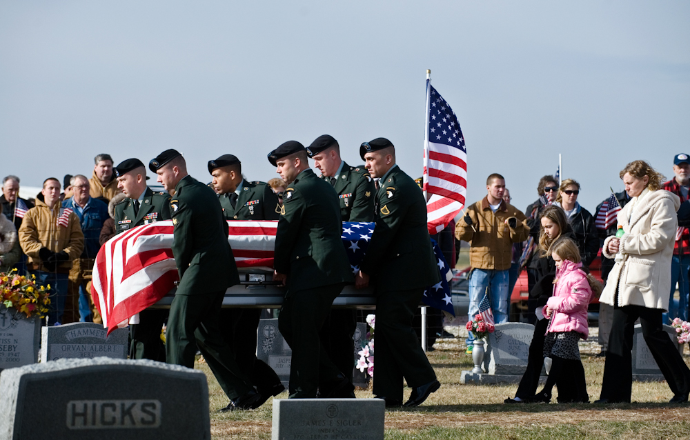 Servicemen carry the casket of Army Sgt. Barry Jarvis, 36, as his wife, Tina, and daughters, Kitaira, 11, and Aleesha, 8, walk behind at the Deer Creek Baptist Church Cemetery in Tell City, Ind.