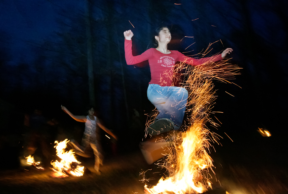 Gloria Emrani, 13, right, and Aida Emamghorashi, 8, left, leap over four consecutive fires during a celebration of the Persian New Year, or Norooz, in Greensboro on Tuesday, March 13, 2007. Jumping over the fire is supposed to cleanse the jumper so that they can start the New Year with a purified mind, body, and soul.