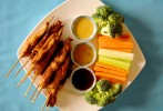 Grilled chicken on a stick with raw vegetables and dipping sauces.
