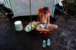 Chris Tuliano tries to stay dry in his camp after recent rains.