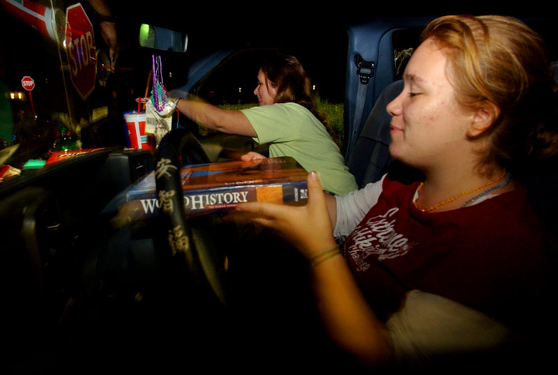 After finishing her homework, Brandi Covey, 16,  tries to find space to store her World History textbook in the Ford Aerostar van that she lives in with her mom, Bethany, back,  her mother's boyfriend, Steve Poteat, not pictured, and their friend, Marty Robbins,  not pictured.  They also have a cat, Gypsey, and a dog, Chase Allen, that share their space in the van.  The family became homeless after their rental home was destroyed by hurricanes.