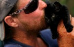 Rick Orand, who lives in a group  homeless camp behind a shopping center in Vero Beach, kisses the new camp kitten, Inky.  The kitten was thrown from a moving car when Karen Eurich, who also lives in the camp, picked it up and brought it back to camp.  Even though there isn't much food, Orand and Eurich manage to find scraps of food for the kitten to eat.