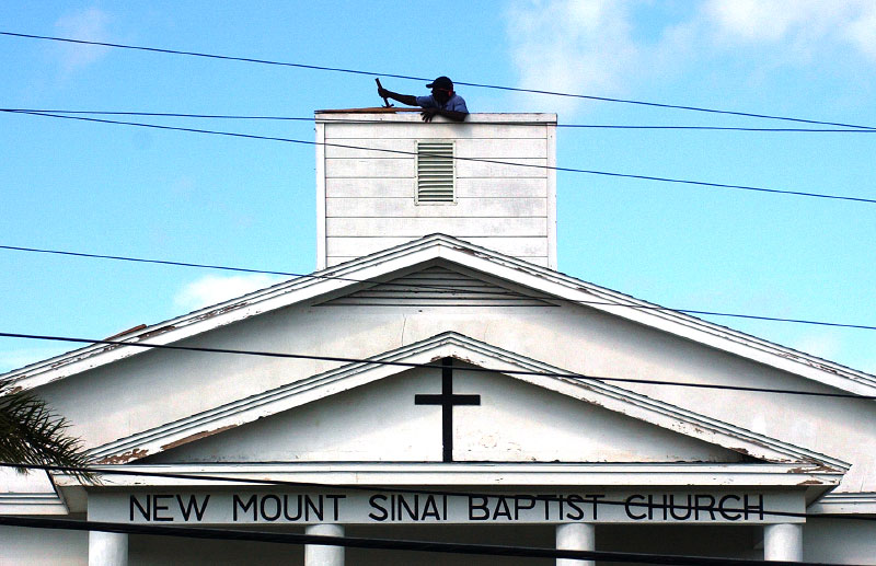 Thomas Hamm, a member of the New Mount Sinai Missionary Baptist Church in Gifford, Fl., clears debris from the steeple of the church on Monday, September 27, 2004.  Hurricane Jeanne caused only minor damage to the church.