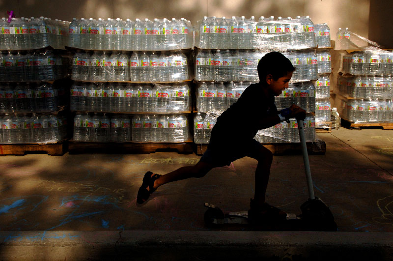 Manolo Naredo, 7, of Metairie, Louisiana, passes his time at a Red Cross shelter at the Central Baptist Church in Crestview, Florida, by riding a donated scooter past stacks of donated water.  Naredo and fifteen of his relatives fled Hurricane Katrina and stayed in hotels until they started to run out of money.  The police then referred them to this Red Cross shelter.