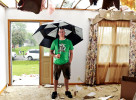Wes Mofield tries to stay dry as he stands in his grandmother's living room at 106 S. Weber Drive in Haubstadt, Ind. Family members believe a tornado hit the home when a line of severe storms blew through the area the night before.