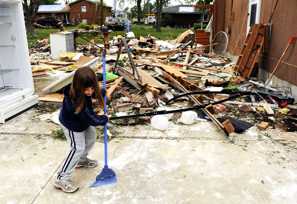 Whitney Johnson, 6, cleans up around some of the destruction at her grandmother's home at 106 S. Weber Drive in Haubstadt, Ind. Family members believe a tornado hit the home when a line of severe storms blew through the area the night before.