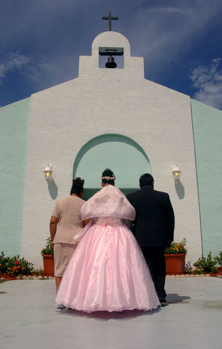 Evelia's parents, Carmen, left, and Ramiro, right, escort her into Our Lady of Guadalupe church in Fellsmere.  Walking into the church Evelia is considered a child.  When she leaves she will be considered a woman.