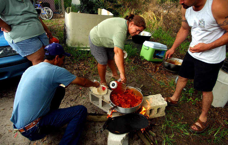Evelia's mother, Carmen, cooks asado de puerco, or pork with chili sauce, over an open fire outside their home in Fellsmere on the morning of the quinceanera.  Family and friends helped prepare five homemade dishes that fed hundreds of guests at the reception.