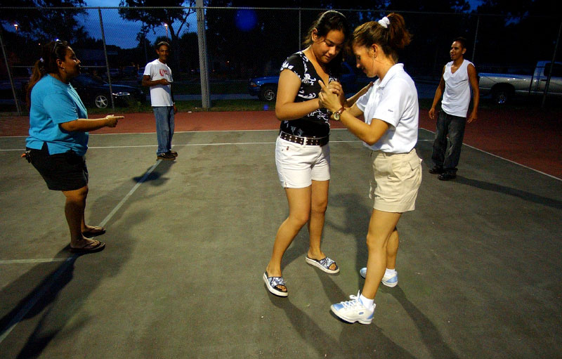 Esperanza Lopez, right, works with Evelia, center, on some dance moves during a dance session with her escorts, or chambalanes, at a public tennis court in Fellsmere a month before the quinceanera.