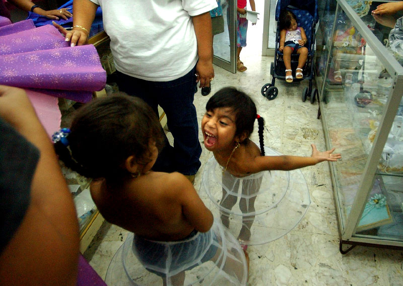 After four days of shopping outside in the 102 degree heat in Monterrey, Mexico, Kenya Cantu, 4, takes out her frustrations on her cousin, Eliamar Solis, 4, between trying on dresses for the quinceanera.  Some dress shops are so small that they don't have dressing rooms, so the girls have to try on dresses in the entryway.