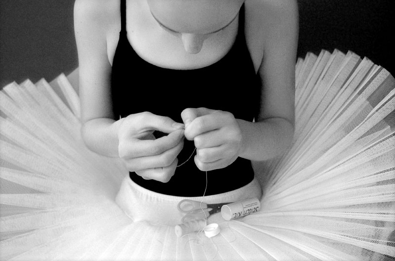 Hope Gaines, 13, takes time out from ballet practice at the Spine and Sport Institute in Vero Beach, Fl., to thread a needle to sew up the ribbons on her satin pointe shoes, which unravel often.  At 13, Gaines is one of the youngest members of the advanced class at Ballet Vero, a classical career-oriented ballet academy.  She and other members of the advanced class are models for the  younger girls.
