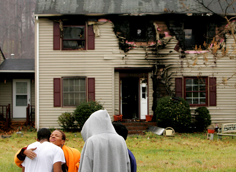 Winifred Phillips, who is renting the home at 4901 Shady Pine Drive in Greensboro, is comforted by friends and neighbors after the home caught fire on Wednesday, December 13, 2006.  Phillips sustained minor burns to her hand but was otherwise unharmed.