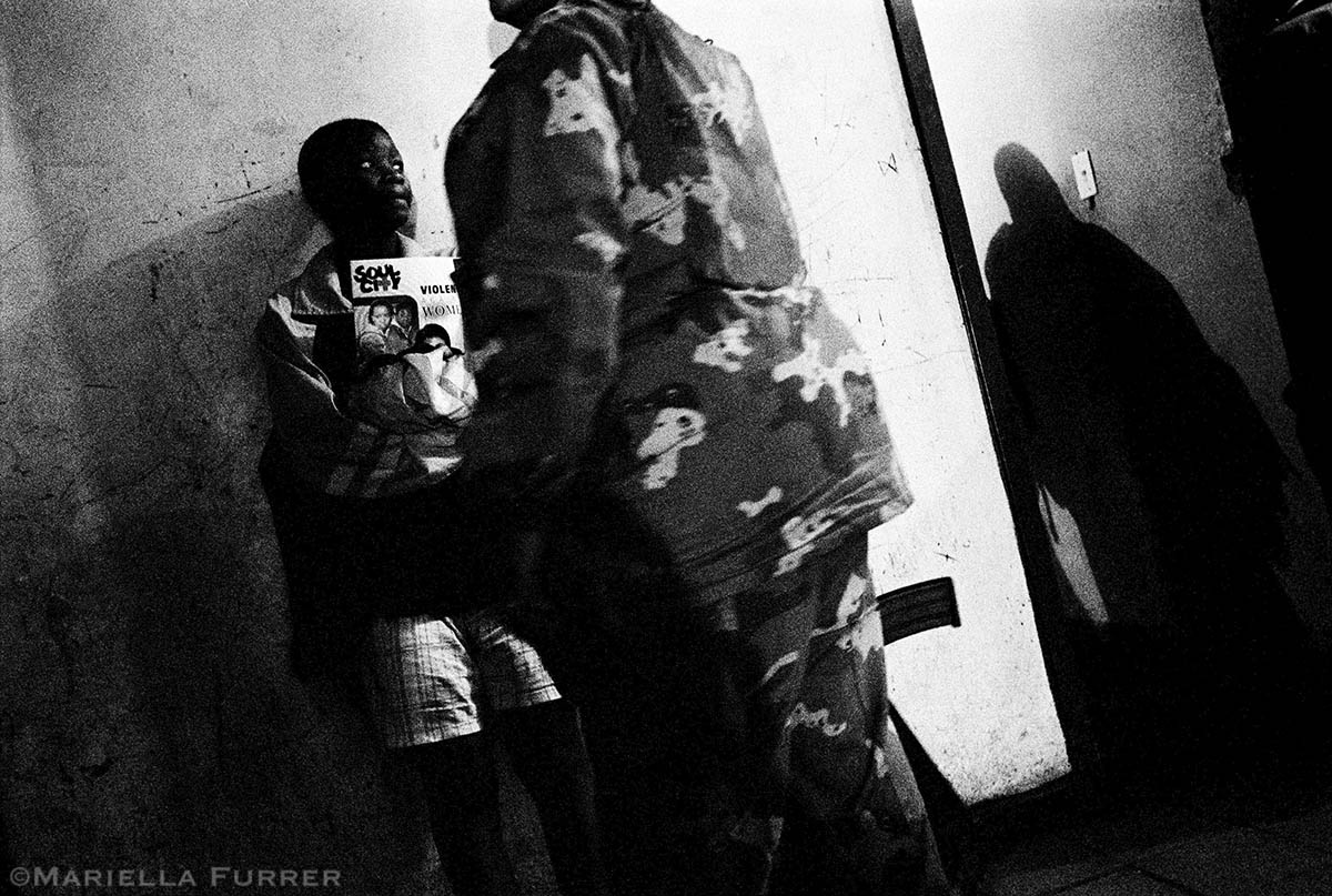 A teenage girl discovered to be living with a much older man during a night raid on her building in Hillbrow waits to be taken to a safe house. PLACE: JohannesburgDATE: December 2002