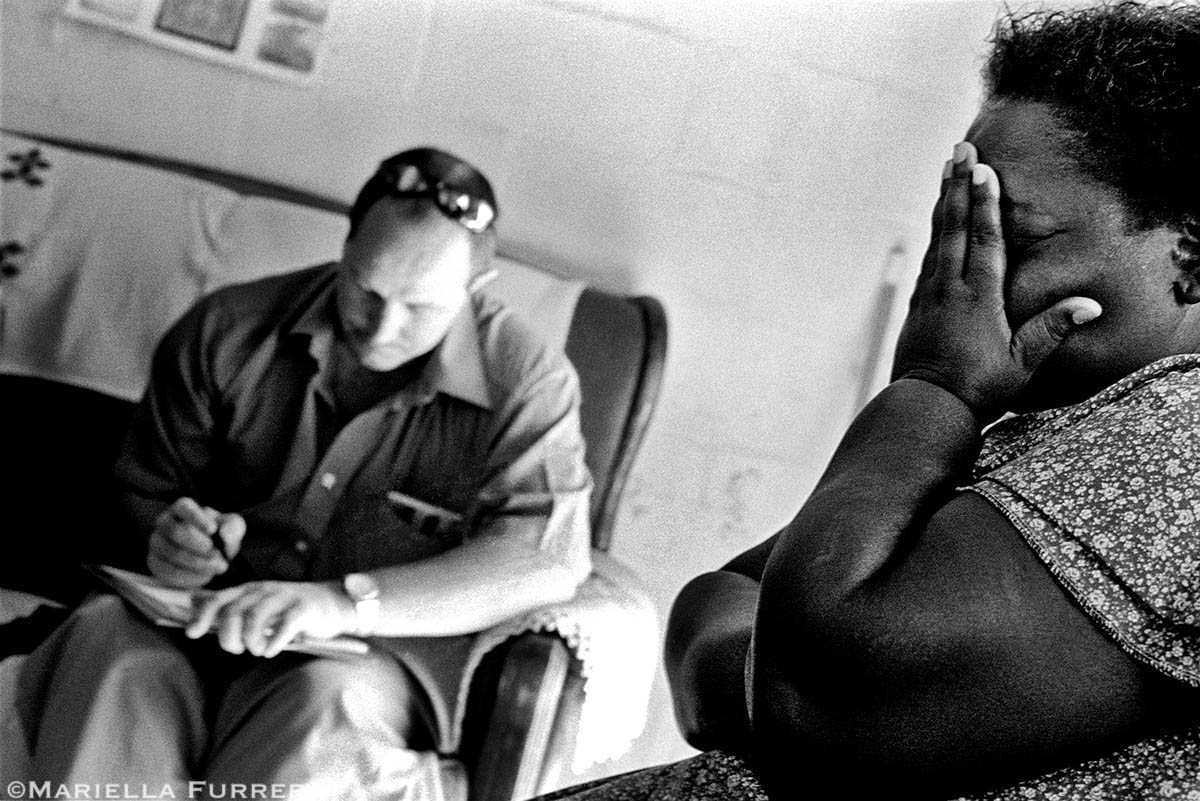A distraught mother listens to Inspector Theo Steyn of the Police Child Protection Unit as he takes a statement from her son, 11, who admitted to sexually abusing his 8-year-old niece, her granddaughter. The boy was put into a diversion programme for young sex offenders. PLACE: Delft South, Western CapeDATE: March 2004