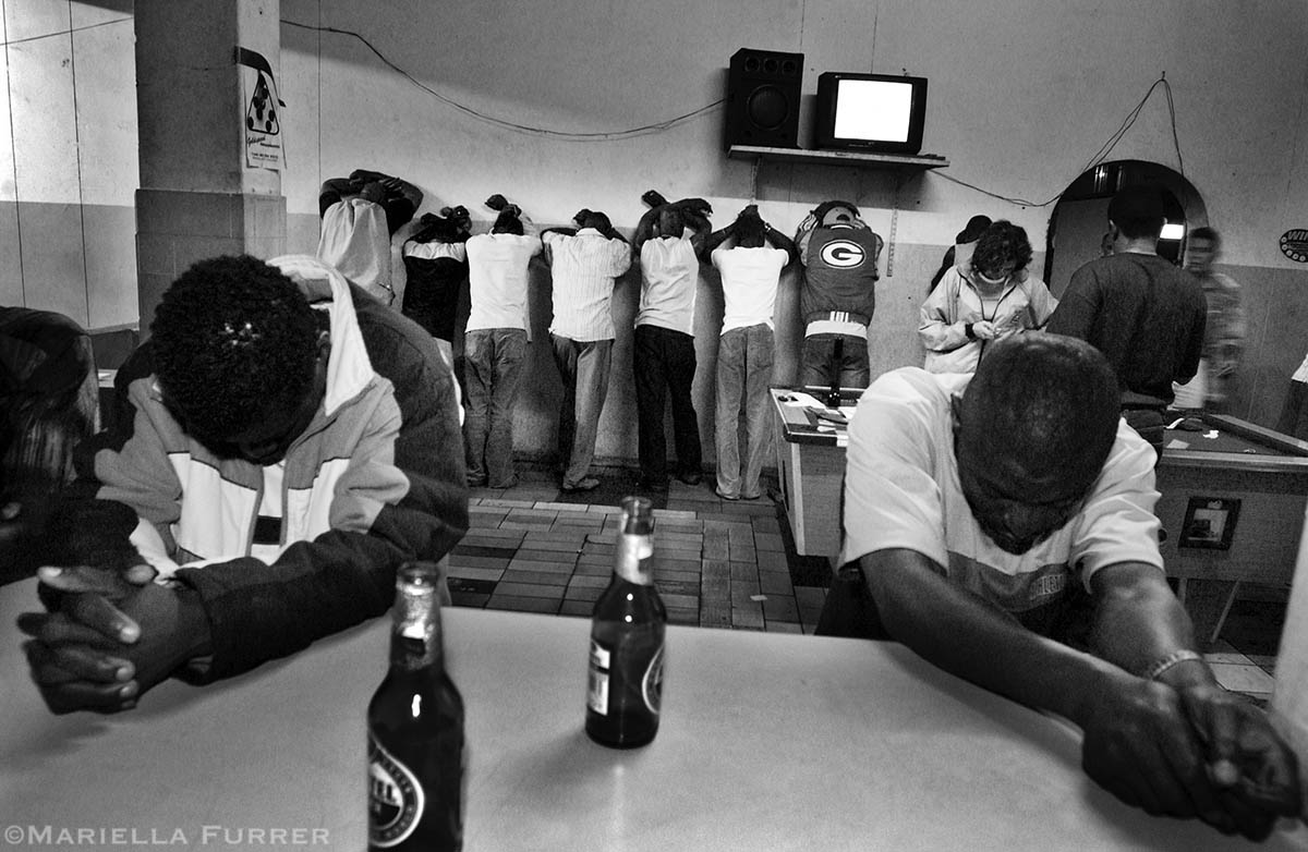 Customers at a bar frequented mostly by Nigerians, some of who are suspected of being pimps forcing children into prostitution, are held by police during a night raid, while they search through their phones and wallets for any information. PLACE: JohannesburgDATE: November 2004