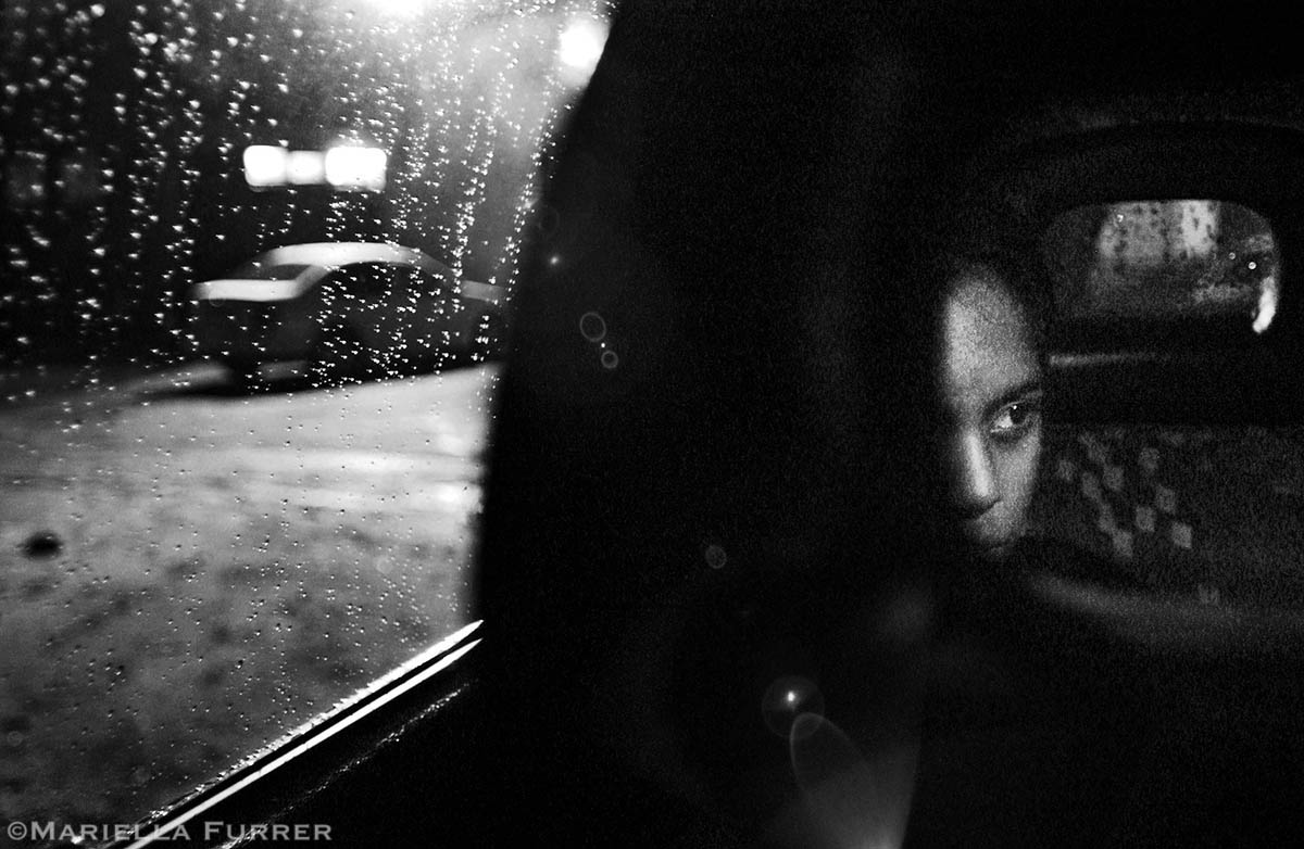 Jennifer, 13, sits in a police car after being rescued during a night raid. Abducted in Durban, she had been brought to Johannesburg and forced into the sex trade. She said she had not been made to work yet, but alleged that the pimp and another man spiked her drink and raped her. PLACE: GermistanDATE: November 2004