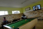 A ten year old boy watches cartoons on TV as another patient plays pool in the social room of the Sunshine Ward. The boy is the only child infected with extremely drug resistant (XDR) TB. His mother who was HIV positive and also infected with XDR died in the ward a month previously. He lives in a female room of the ward.