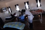 A nurse wheels a patient to his bed in the male High Care Unit the Sunshine Ward Prior to falling sick, he  worked with the Ministry of Education. He has been at the Jose Pearson TB Hospital for 2 years. First he was admitted with multi-drug resistant (MDR) TB, but was then moved to the XDR ward. His wife, a domestic worker, who lives over an hour away visits him several times a week.