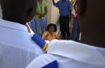 Security guards try to deal with unhappy patients who are sitting on the rails of a newly installed security gate preventing vehicles from leaving the hospital premises.