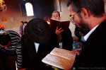 Jewish pilgrims pray from the Torah at the tomb of Rabbi Abu Hatzeira where  food, water and other personal effects have been placed for blessing.